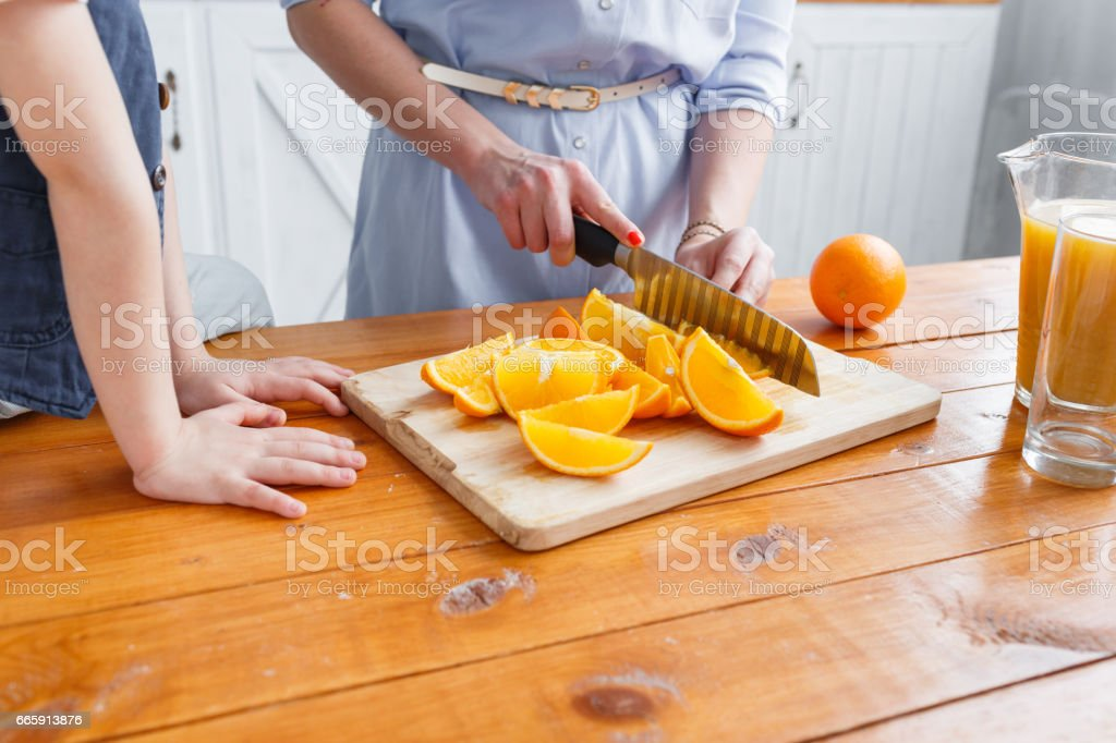 Mom cuts fruit to her son. sliced oranges on a wooden cutting board. Healthy and tasty breakfast foto stock royalty-free
