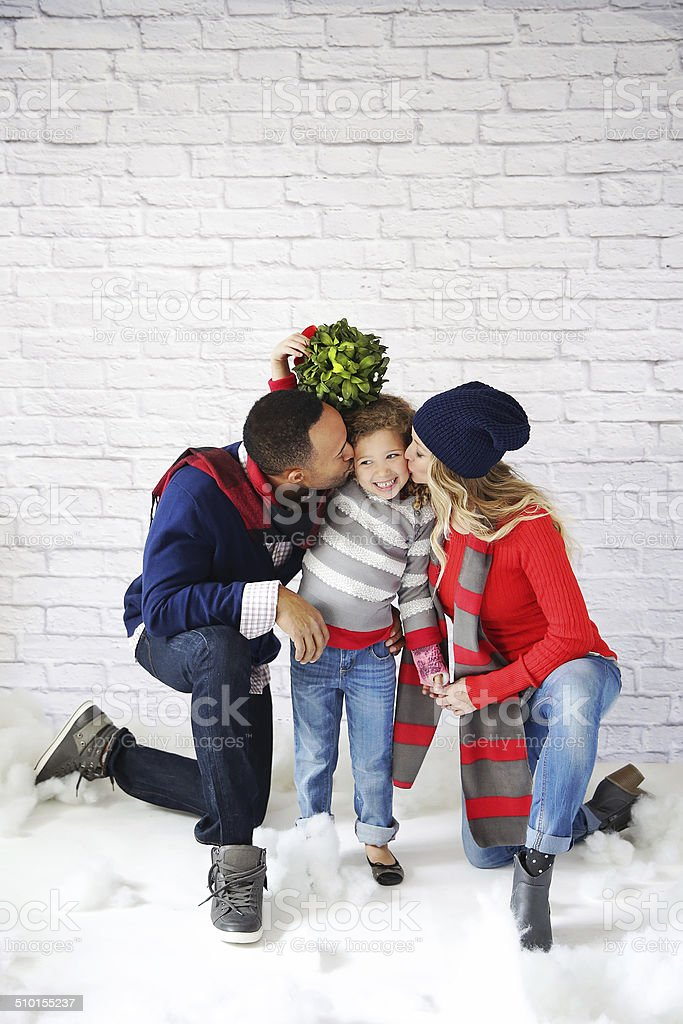 Mom Dad and Child under mistletoe stock photo