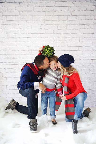 Mom Dad and Child under mistletoe stock photo