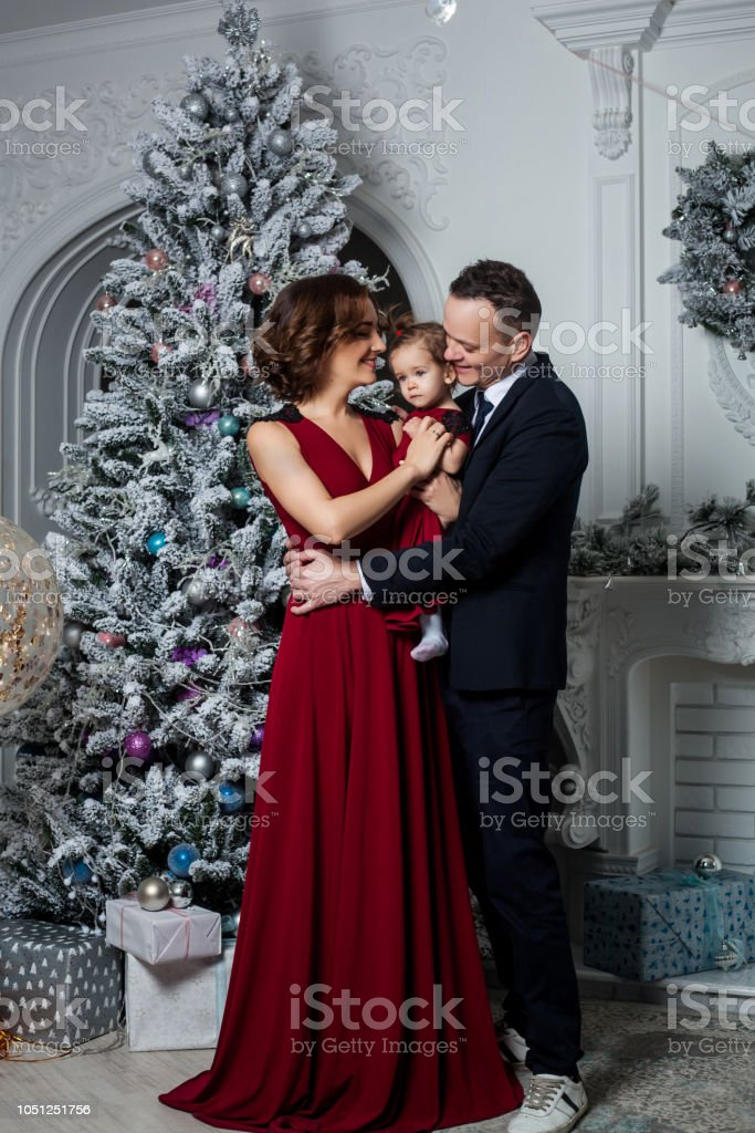 Mom dad and daughter dressed in a stylish suit and elegant red evening dress at a secular party in honor of the New Year stock photo