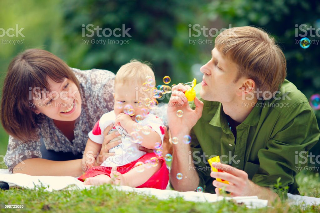 Mom, Dad and little baby are lying on the grass and blowing bubbles stock photo