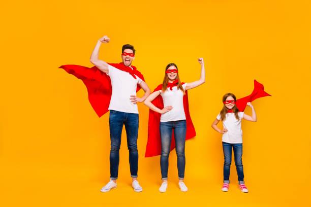 mamma pappa och liten foxy lady spelar seriefigurer bär superhjälte uddar isolerad gul bakgrund - superwoman barn bildbanksfoton och bilder