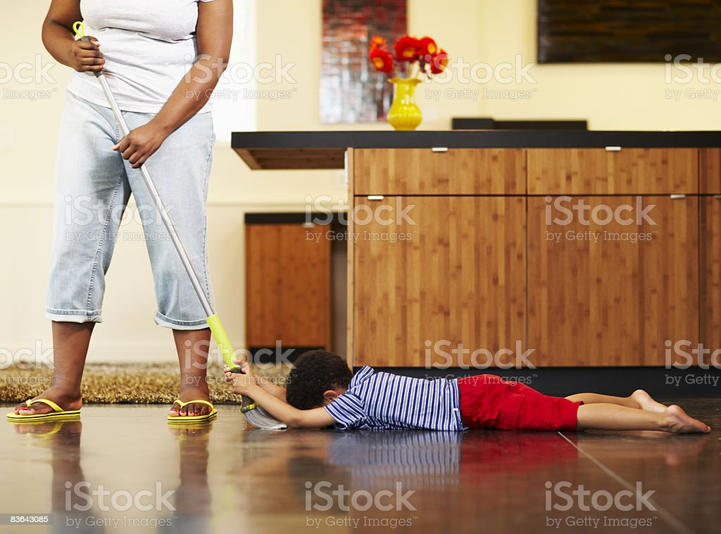 mom dragging boy across floor with broom stock photo