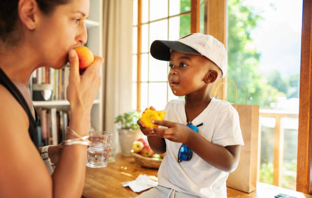 Mom eating a peach with her cute little boy at home stock photo