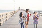 An attractive Filipino mom and her two children eat ice cream cones as they walk down a California boardwalk by the beach