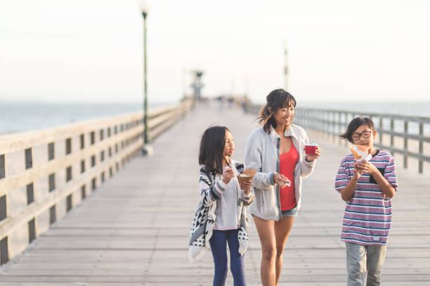 Mom eating ice cream with her kids on a beach boardwalk An attractive Filipino mom and her two children eat ice cream cones as they walk down a California boardwalk by the beach boardwalk stock pictures, royalty-free photos & images