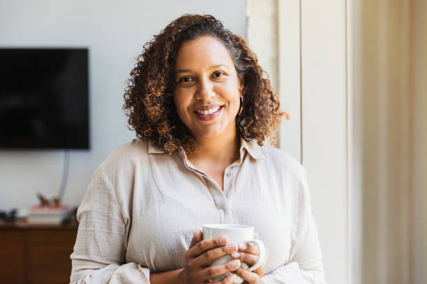 Mom enjoys cup of coffee in morning stock photo