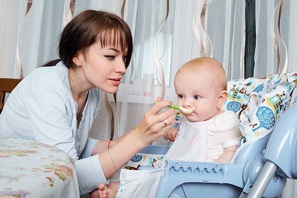 Mom feeds the baby at  table with spoon. Healthy eating, stock photo