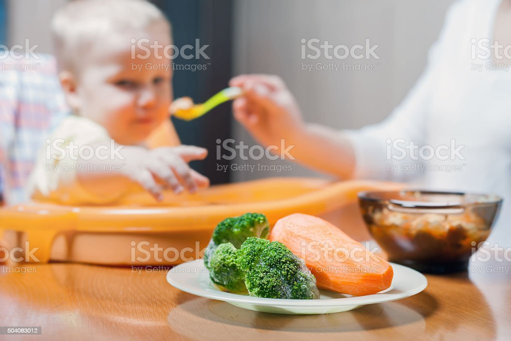 Mom feeds the baby soup. Healthy and natural baby food stock photo