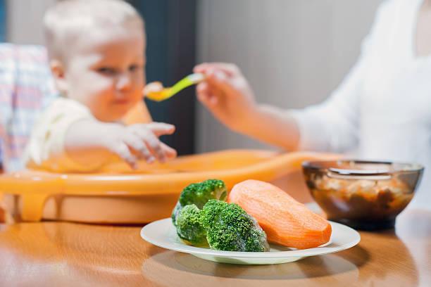 Mamá comparte la sopa de bebé. Bebé de alimentos sanos y naturales - foto de stock