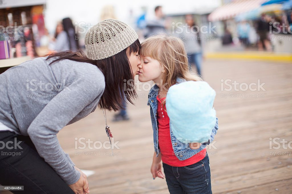 Mom Gives Daughter a Kiss stock photo