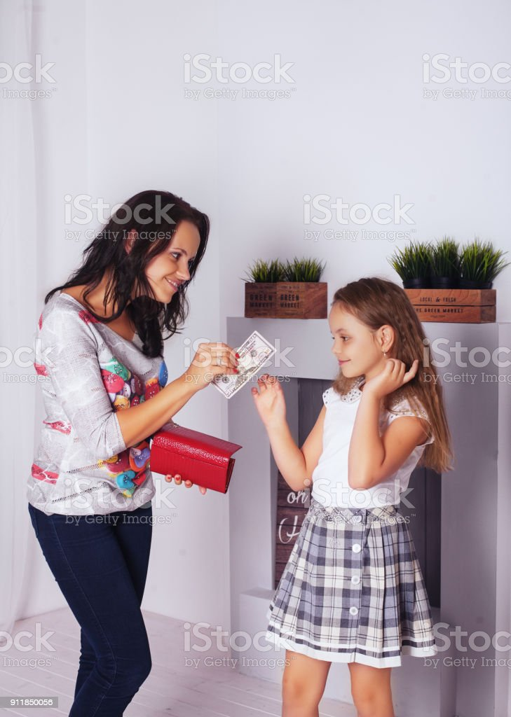 Mom gives pocket money daughter. The concept of family and lifestyle stock photo