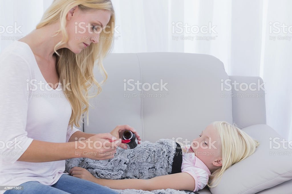 Mom giving her daughter medicine royalty-free stock photo