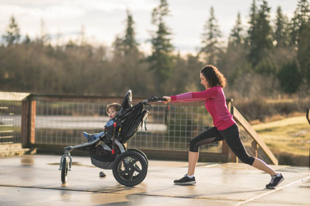 Mom Goes Jogging with Infant in Stroller stock photo