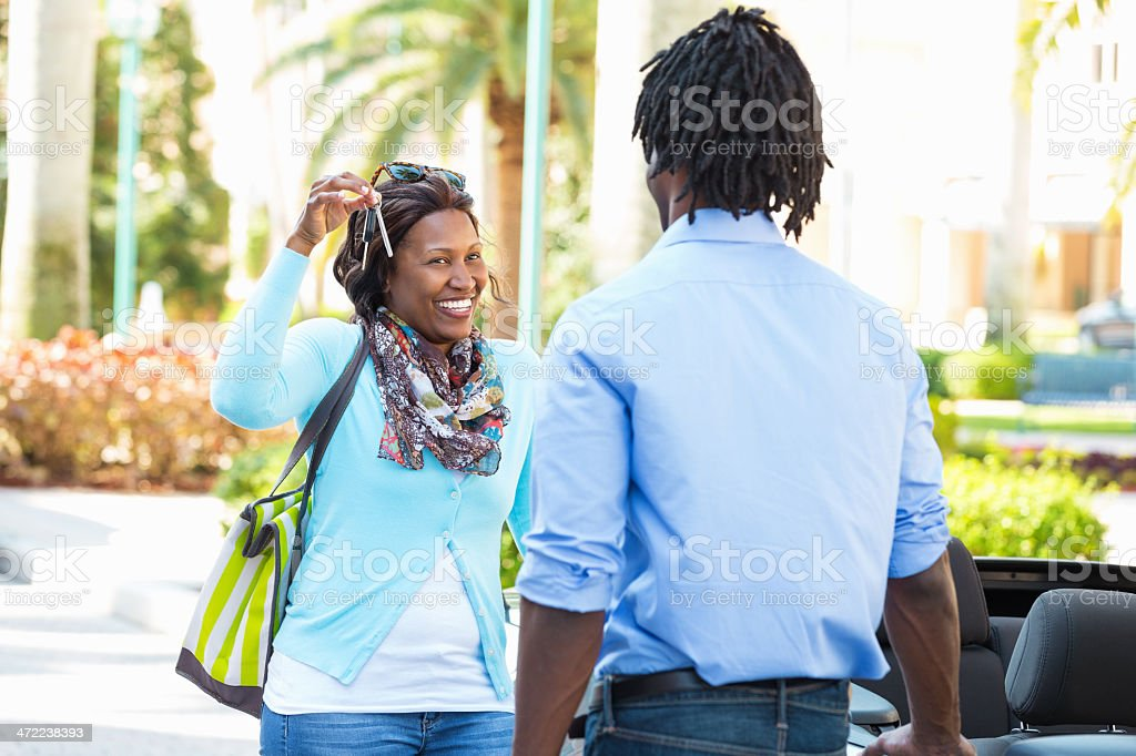 Mom handing new car keys to her young son stock photo