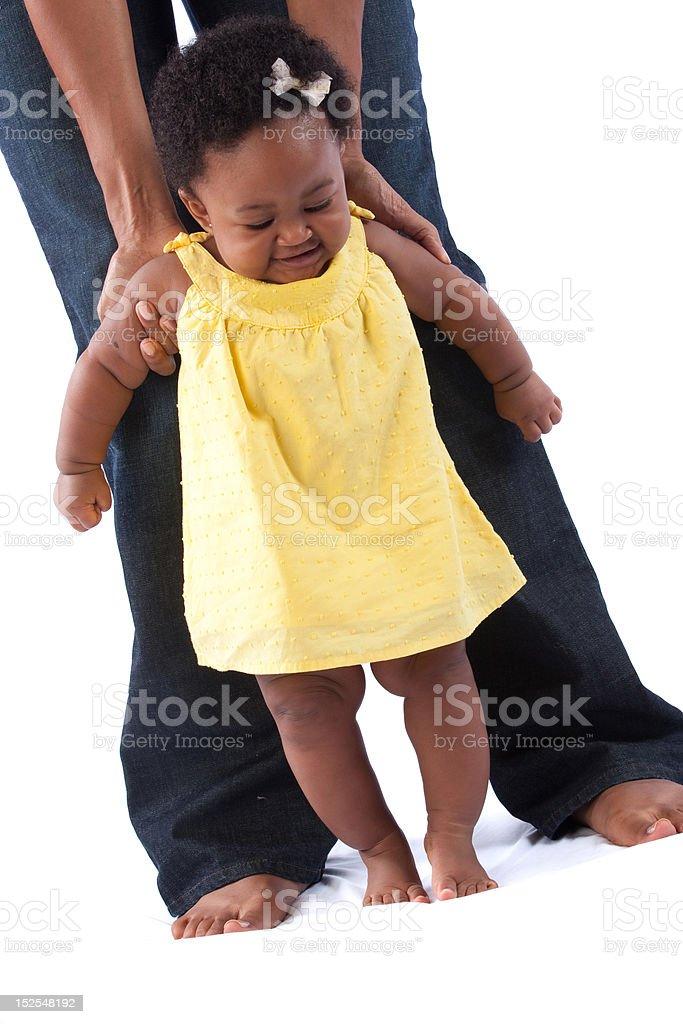 mom helping child walk stock photo