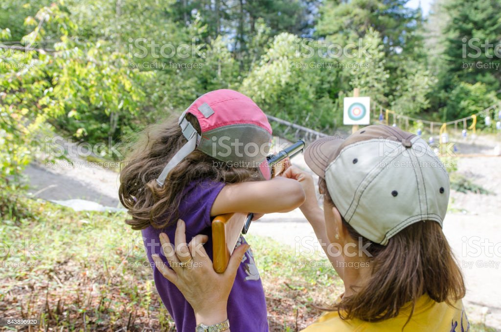 Mom helping her daughter while aiming at target with rifle during outdoors summer day vacations stock photo