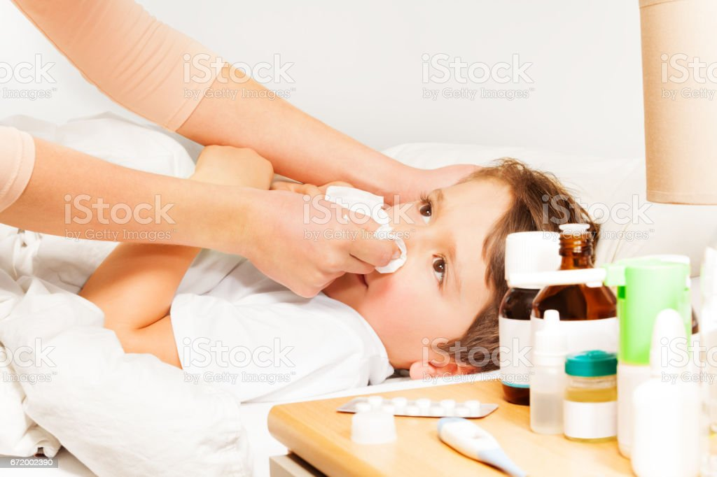 Mom helping her kid to blow his nose with napkin stock photo