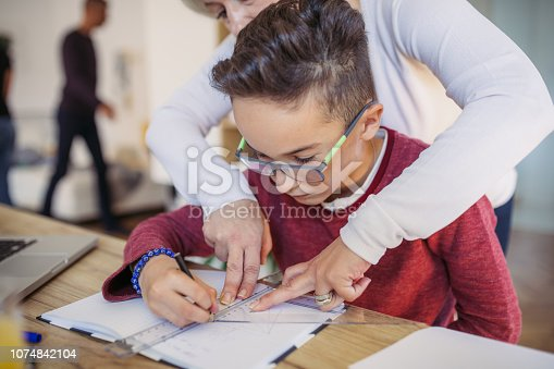 680535874 istock photo Mom helping son with math 1074842104