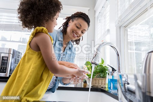 Beautiful mom and her adorable daughter wash their hands after baking in the kitchen.