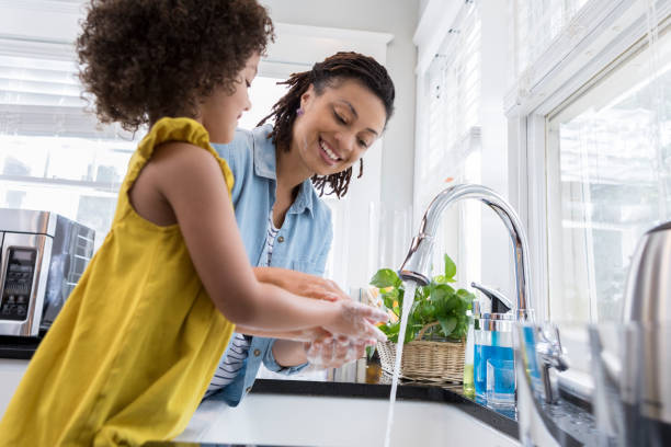 mom helping young daughter wash hands - kitchen sink stock photos and pictures