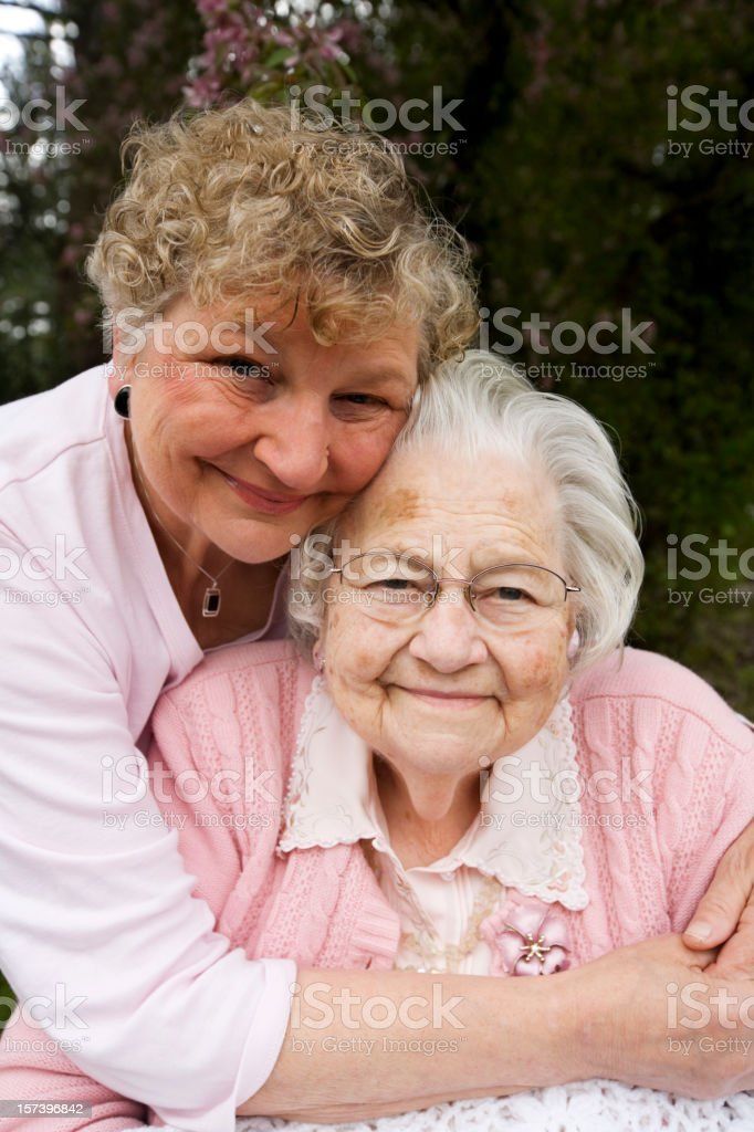 Mom holding GrandMother 80 years retired caregiver love old stock photo