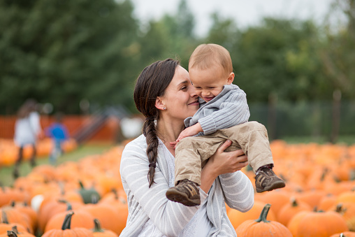 An attractive young mother holds up by her face and nuzzles his cheek. He is laughing and smiling. They are surrounded by hundreds of pumpkins.