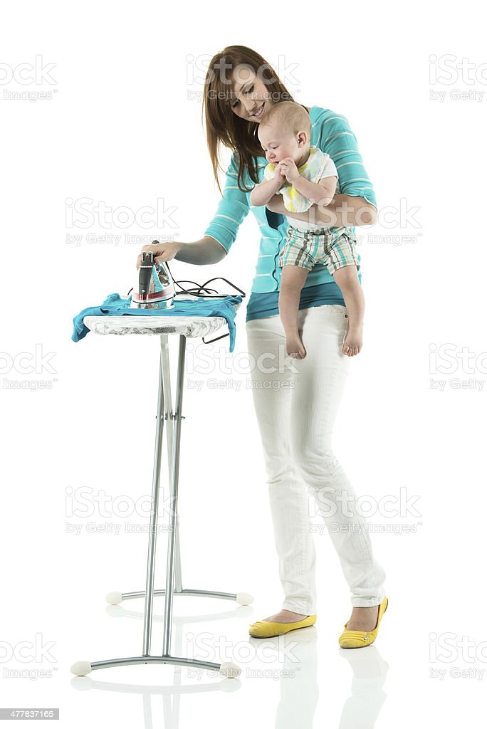 Mom ironing clothes while carrying her baby royalty-free stock photo