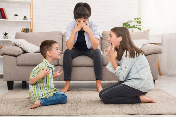 Mom is depressed by screaming children, siblings having quarrel Problems of motherhood. Mom is depressed by screaming children, siblings having quarrel arguing stock pictures, royalty-free photos & images
