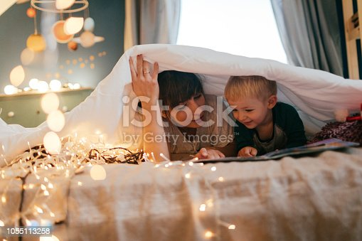 Photo of a little boy listening to a bedtime stories, that his mother is reading in the nursery