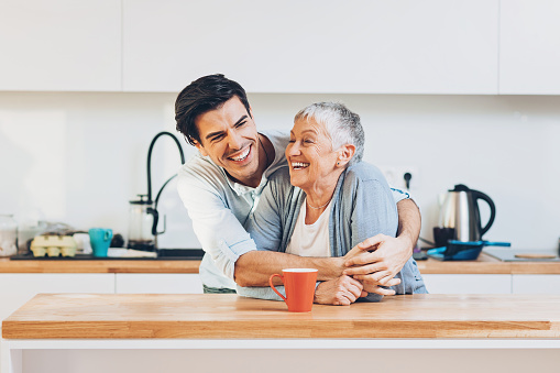 Senior woman and young man embracing in a domestic kitchen