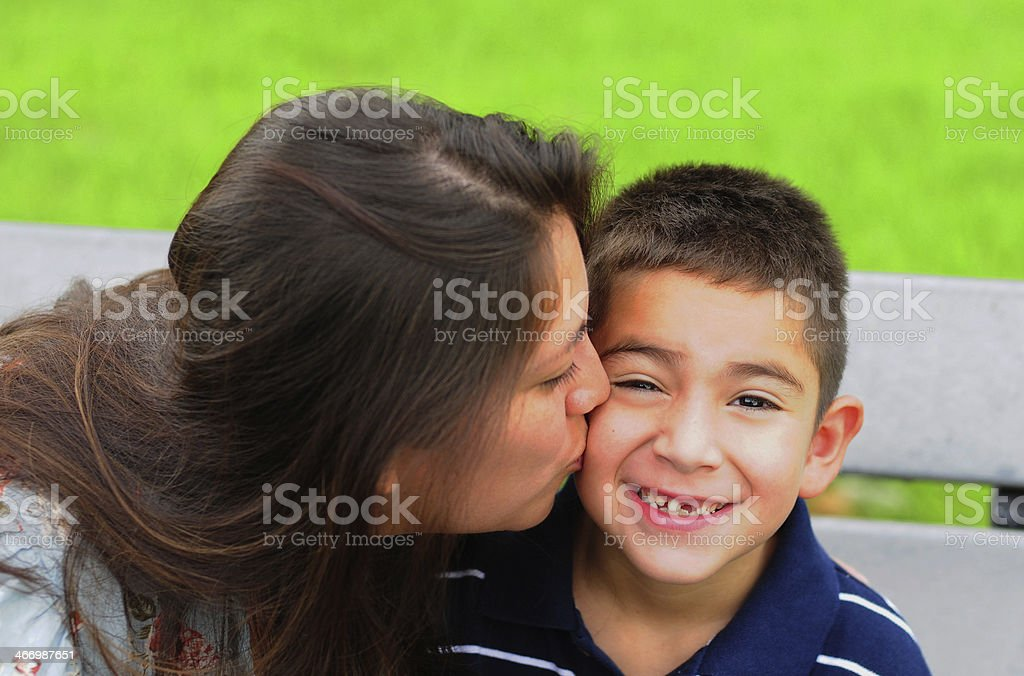 Mom kissing young son on cheek stock photo