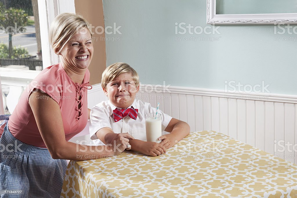 Mom laughing, boy crying stock photo