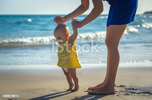 Mom learns to walk little baby on the sand at the beach