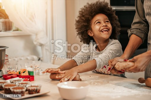 Cute 5 years old girl making cookies for Christmas with her mom.