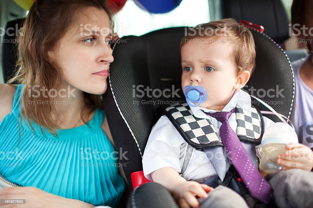 Mom looking at her son in child safety seat stock photo