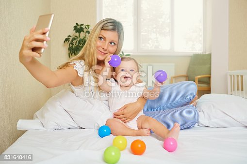 istock Mom makes a photo on the phone with the baby in the room. Salfie 831640416