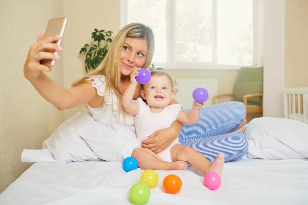 mutti macht ein foto auf dem handy mit dem baby im zimmer. salfie - lustige babybilder stock-fotos und bilder