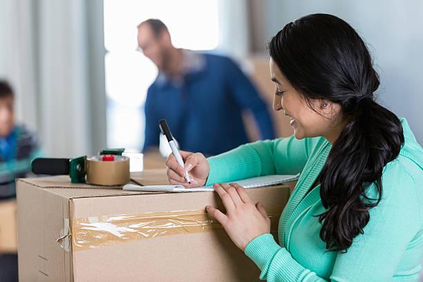 mutter macht liste während der vorbereitung, um auf neue zuhause - umzug checkliste stock-fotos und bilder