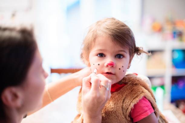 mom making up her cute little girl for halloween - manonallard stock photos and pictures