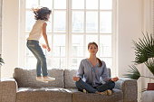 istock Mom meditating on couch ignore kid jumping near 1164802848
