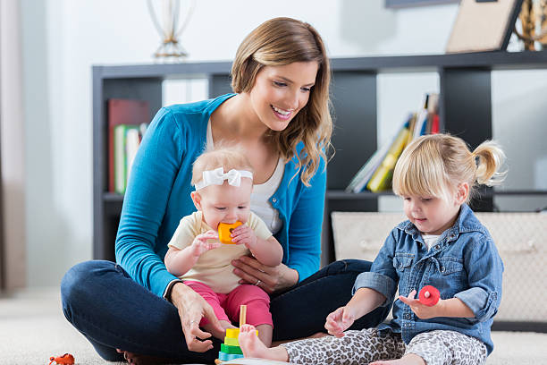 Mom or nanny plays with children at home - foto de stock