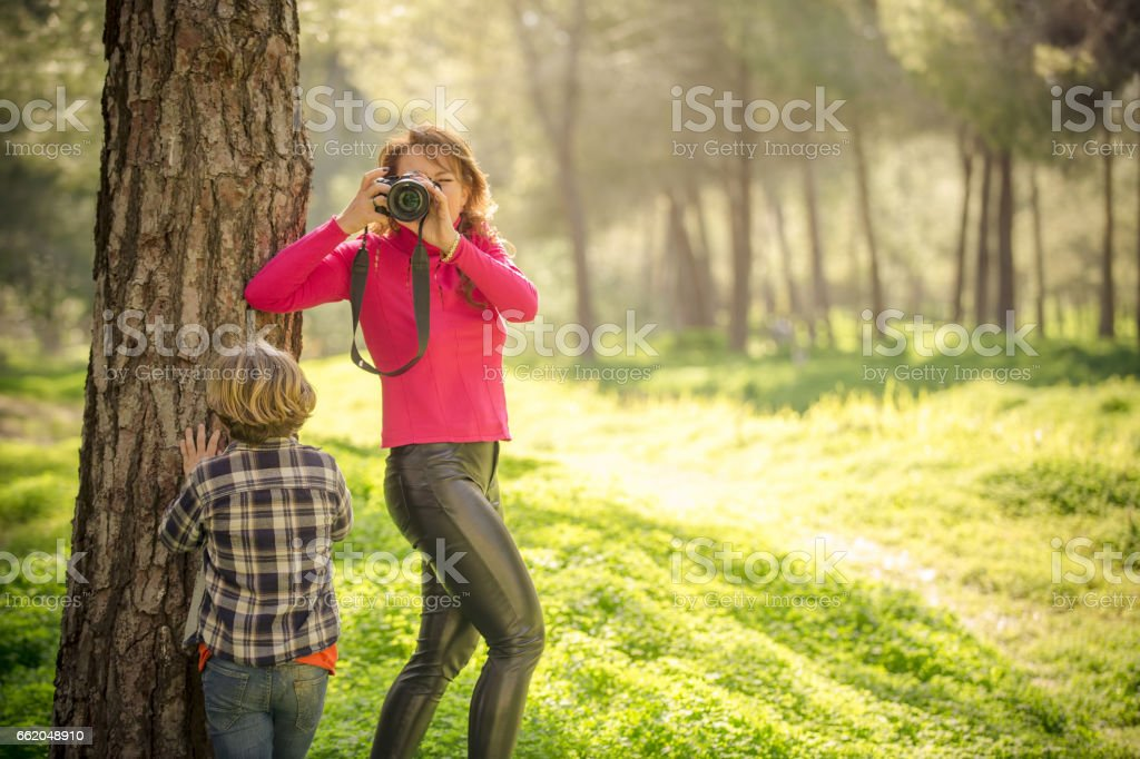 Mom photographing her son in green park royalty-free stock photo