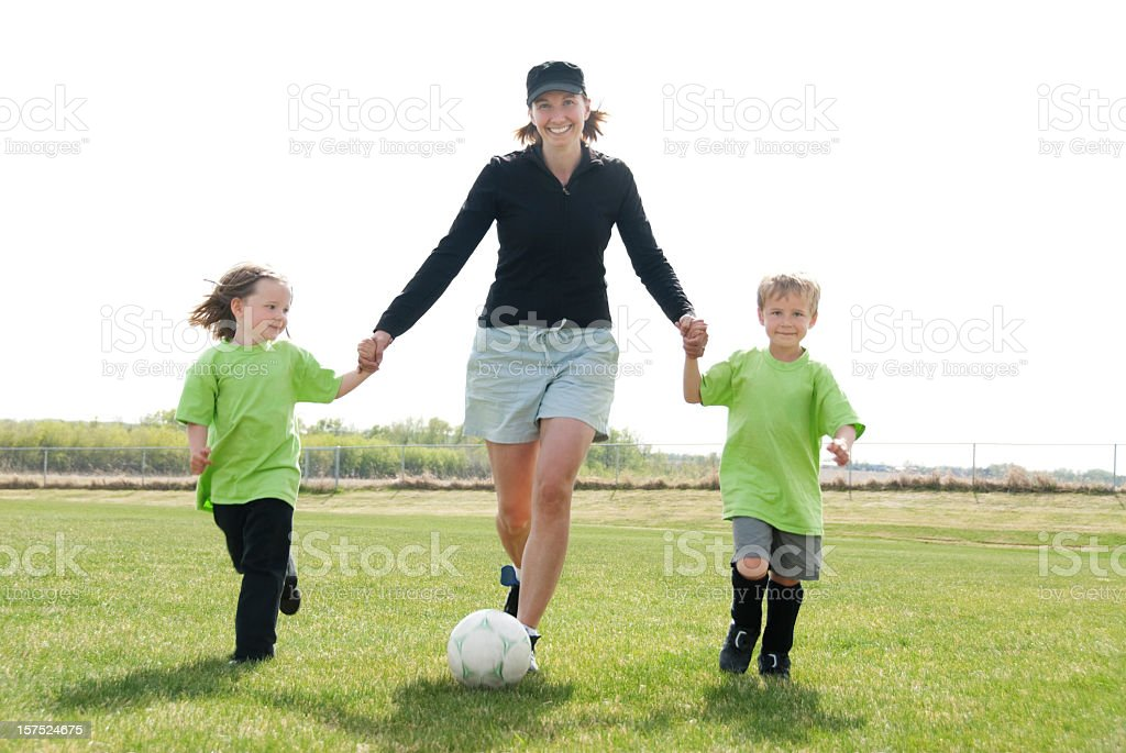 A mom playing soccer with her two children  stock photo