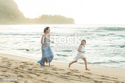 A vibrant mom chases her young daughter along the beach by the waves in the late evening. They both have big smiles.