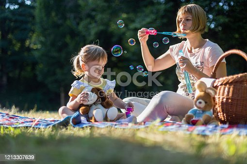Young kid sitting by a woman blowing soap bubbles outdoors