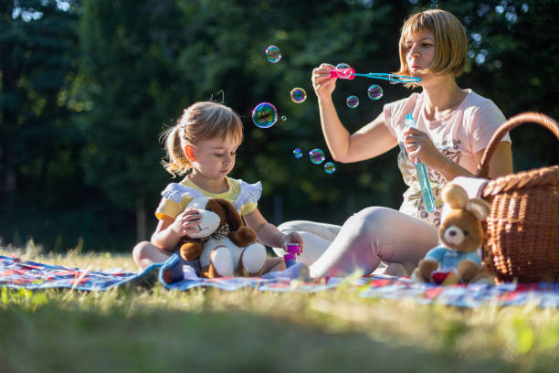 Mom playing with soap bubbles to amuse her daughter on picnic Young kid sitting by a woman blowing soap bubbles outdoors amuse stock pictures, royalty-free photos & images
