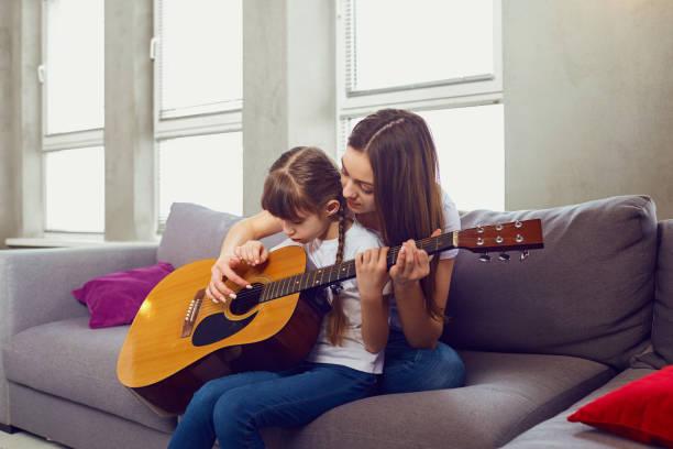 Mutter spielt Gitarre zusammen mit Teenager-Tochter zu Hause – Foto