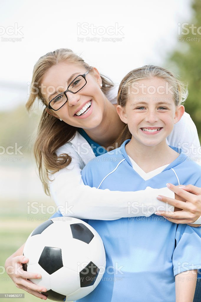 Mom posing with daughter before soccer game stock photo