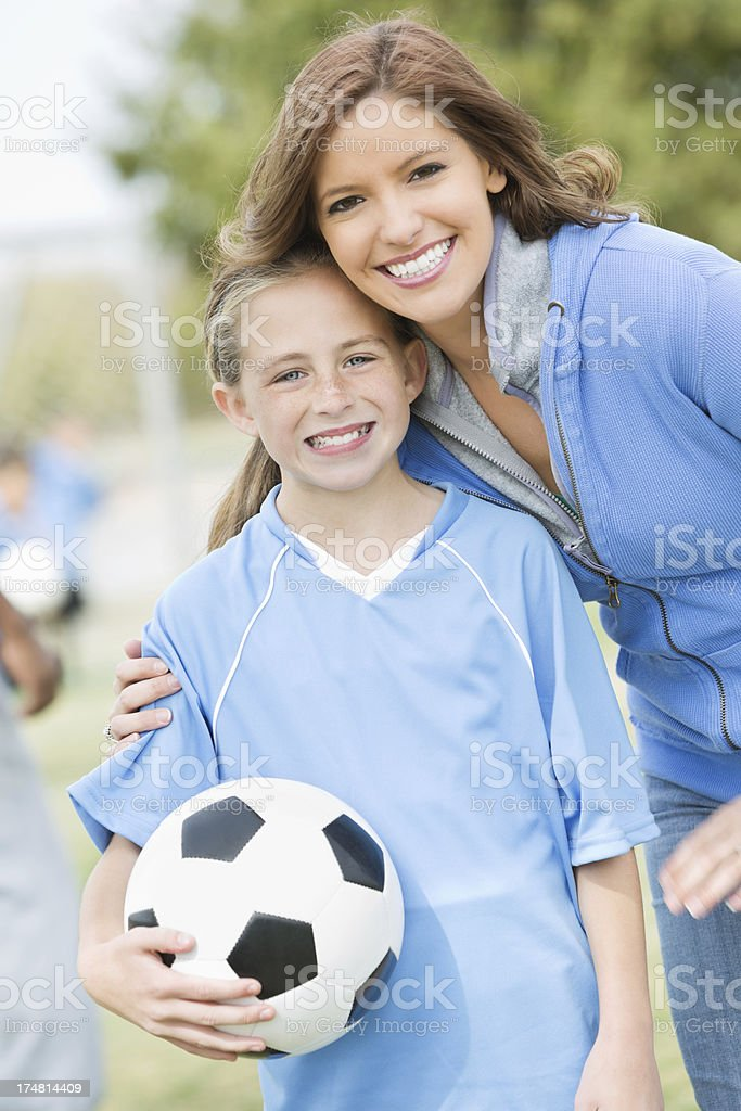 Mom posing with daughter on sidelines of soccer game stock photo